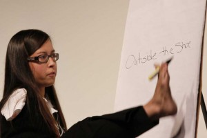 """Using her feet to write out her motto, Jessica Cox says """"Thinking out of the shoe"""" helps motivate her to be persistant to find solution to challenges. Photo by Rob Stapleton"""